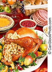 Holiday dinner with roast turkey, pumpkin pie, cranberry chutney, baked ham, dinner rolls and fruits.