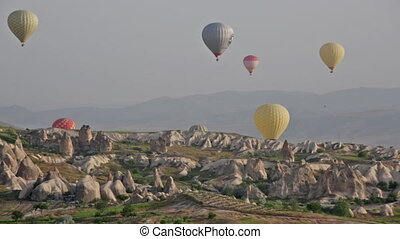 TURKEY, GOREME - MAY 19, 2015 - Multi-colored balloons fly...
