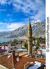 Turkey, Isparta province, beautiful Egirdir lake and the Needle mountain with mosque in winter, vertical frame
