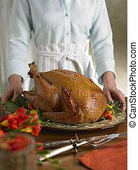 Turkey on a platter - Woman serving a turkey on a platter