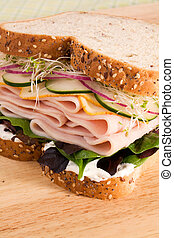 Multi-grain bread filled with sliced turkey, muenster cheese, cucumbers, red onion, alfalfa, lettuce, and an herbed cream cheese spread.