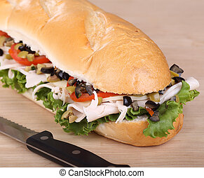 Turkey sub sandwich with cheese, lettuce; tomato; and olives