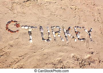 Turkey word written with pebbles on the beach sand in Side, Turkey
