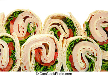 Turkey wrap sandwiches with tomato cheese and lettuce. Viewed from above on a plate.