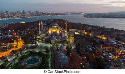 Turkey's largest city at dawn. Aerial view of Hagia Sophia mosque and view of Istanbul in night. Timelaps
