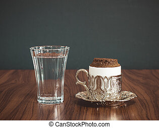 Turkish coffee served with water in traditional copper cup