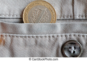 Turkish coin with a denomination of 1 lira in the pocket of beige denim jeans with button