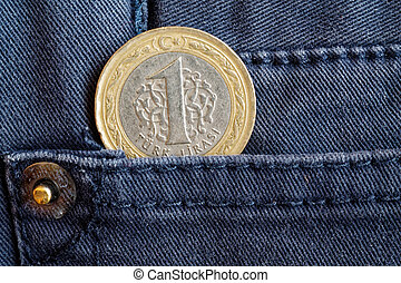 Turkish coin with a denomination of 1 lira in the pocket of gray denim jeans