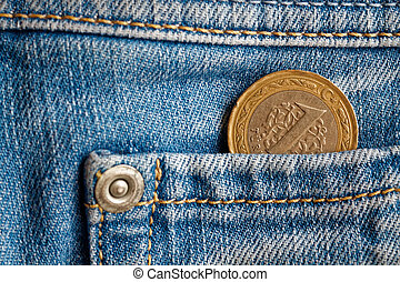 Turkish coin with a denomination of 1 lira in the pocket of light blue denim jeans