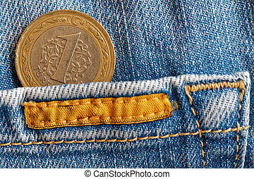 Turkish coin with a denomination of 1 lira in the pocket of old biege denim jeans