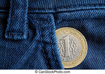 Turkish coin with a denomination of 1 lira in the pocket of old blue denim jeans