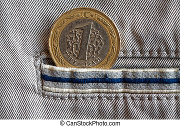 Turkish coin with a denomination of one lira in the pocket of beige denim jeans with blue stripe