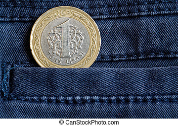 Turkish coin with a denomination of one lira in the pocket of dark blue denim jeans