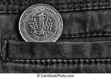 Turkish coin with a denomination of one lira in the pocket of dark denim jeans, monochrome shot