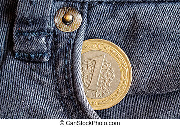 Turkish coin with a denomination of one lira in the pocket of obsolete blue denim jeans