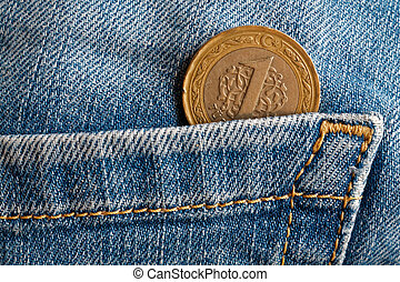 Turkish coin with a denomination of one lira in the pocket of old blue worn denim jeans