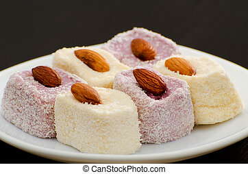Turkish Delight with almonds on a saucer, close-up, black background