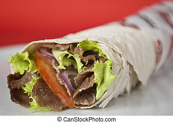 Traditional turkish doner kebab in lavash bread served on white plate