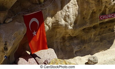 Turkish flag hangs from a rock formation - Close up of a red...