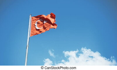 Turkish flag waving in blue sky outdoors