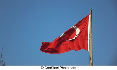 Turkish Flag waving in the wind on a background blue sky. A...