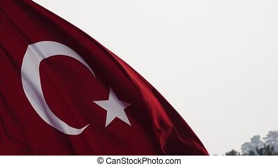 Turkish Flag waving in the wind over blue sky. Close up -...