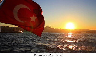 Turkish flag waving on the stern of an Istanbul ship at sunset. Cruising out from Istanbul during sunset. Suleymaniye Mosque in the distance