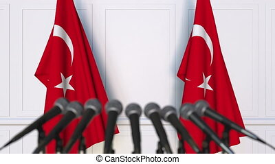 Turkish official press conference. Flags of Turkey and...