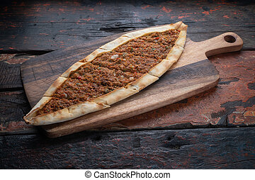 Turkish pide with vegetables on rustic wooden table