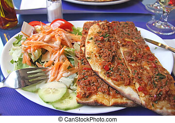 Turkish pizza on plate with mixed salad