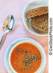 Turkish red lentil cream soup with spices, rye bread on the table in the restaurant. View from above.