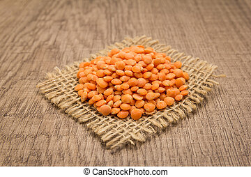 Turkish Red Lentil legume. Grains on square cutout of jute. Wooden table. Selective focus.