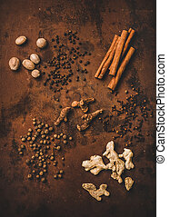 Turkish seven spice Yedi Bahar mix. Flat-lay of black pepper, ginger, cloves, nutmeg, cinnamon, allspice and alpinia root over dark rusty background, top view