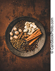 Turkish seven spice Yedi Bahar mix. Flat-lay of black pepper, ginger, cloves, nutmeg, cinnamon, allspice and alpinia root in black plate over dark rusty background, top view