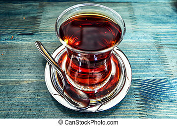 Traditional Turkish tea in glass on blue background