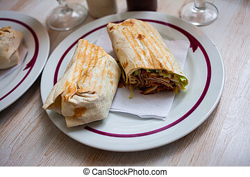 Traditional turkish Durum with meat, vegetables and sauce in lavash flatbread, halved on plate