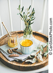 Healthy vegan turmeric latte or golden milk with honey in striped cup on wooden tray, selective focus, vertical composition