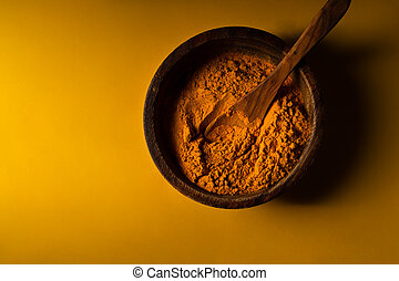 Turmeric powder in wooden bowl with wooden spoon on yellow background. Closeup view. Low key image with copy space