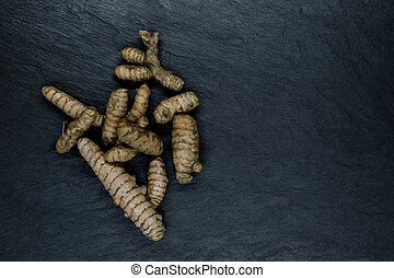 Turmeric Root on Black Stone Background Surface with Free Space