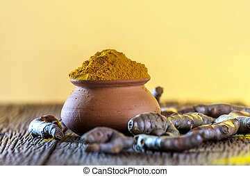 Turmeric roots on wooden background