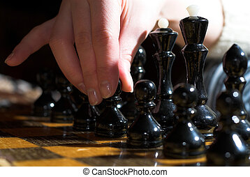 Turn - Young female is pkeying chess, she's making a turn