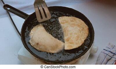 Turn the chebureks in a frying pan with hot oil. Cheburek...