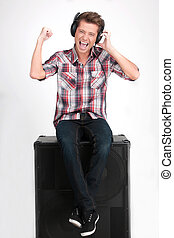 Turn the volume up. Cheerful young man in headphones listening to the music while sitting on the speaker