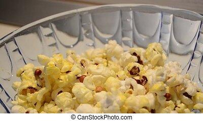 turning around blue glass bowl full of pop corns close up