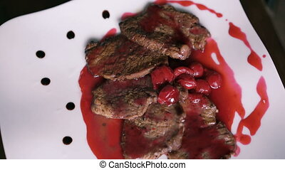 Turning around dish of meat and red sauce on the plate