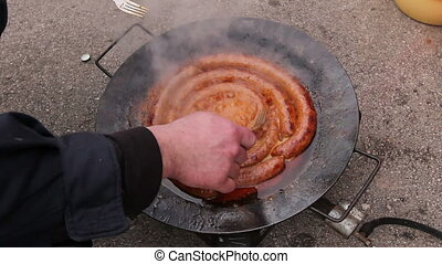 Turning delicious juicy sausages on barbecue plate with...