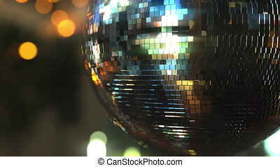 Turning mirror disco ball against bokeh background. Joy, dancing or party concepts