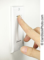 Turning off light switch - Finger turning white light switch...