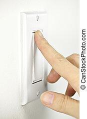 Turning off light switch - Finger turning white light switch...