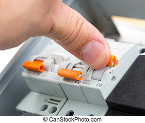 Turning on a fusebox - Hand of an electrician turning on a...